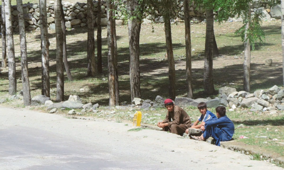 Boys sit on the side of a road to Birgil in Ghizer | Aurangzaib Khan