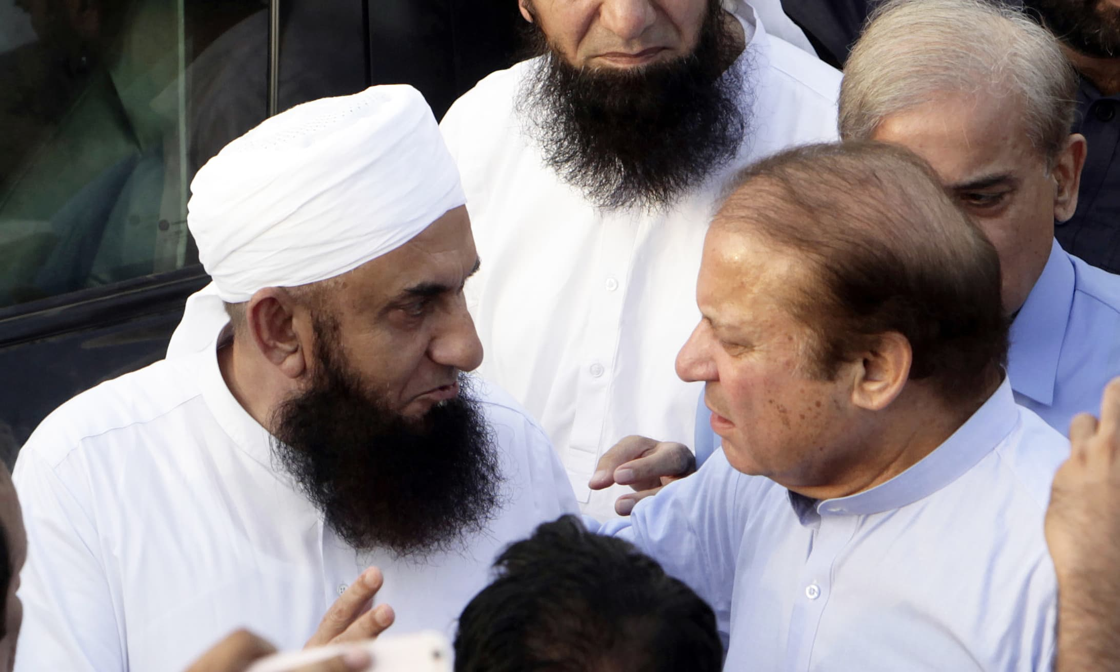 Nawaz Sharif talks with Maulana Tariq Jameel as he arrives to attend the funeral. —AP