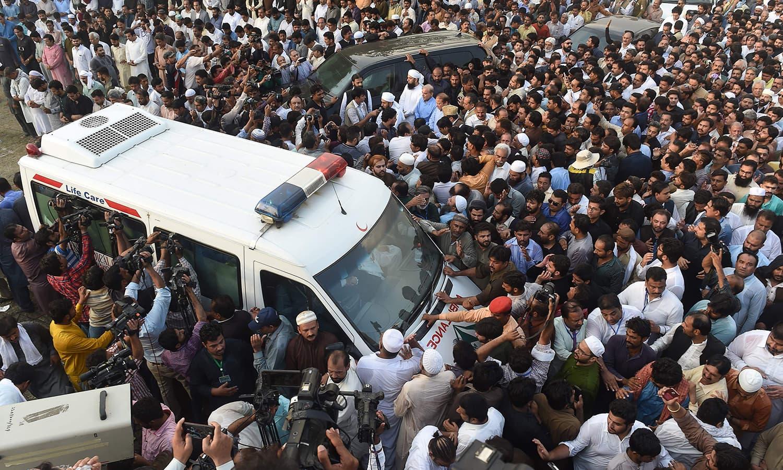 ہزاروں افرا کلثوم نواز کی نماز جنازہ کے بعد ایمبولنس کے قریب موجود ہیں —فوٹو :  اے ایف پی