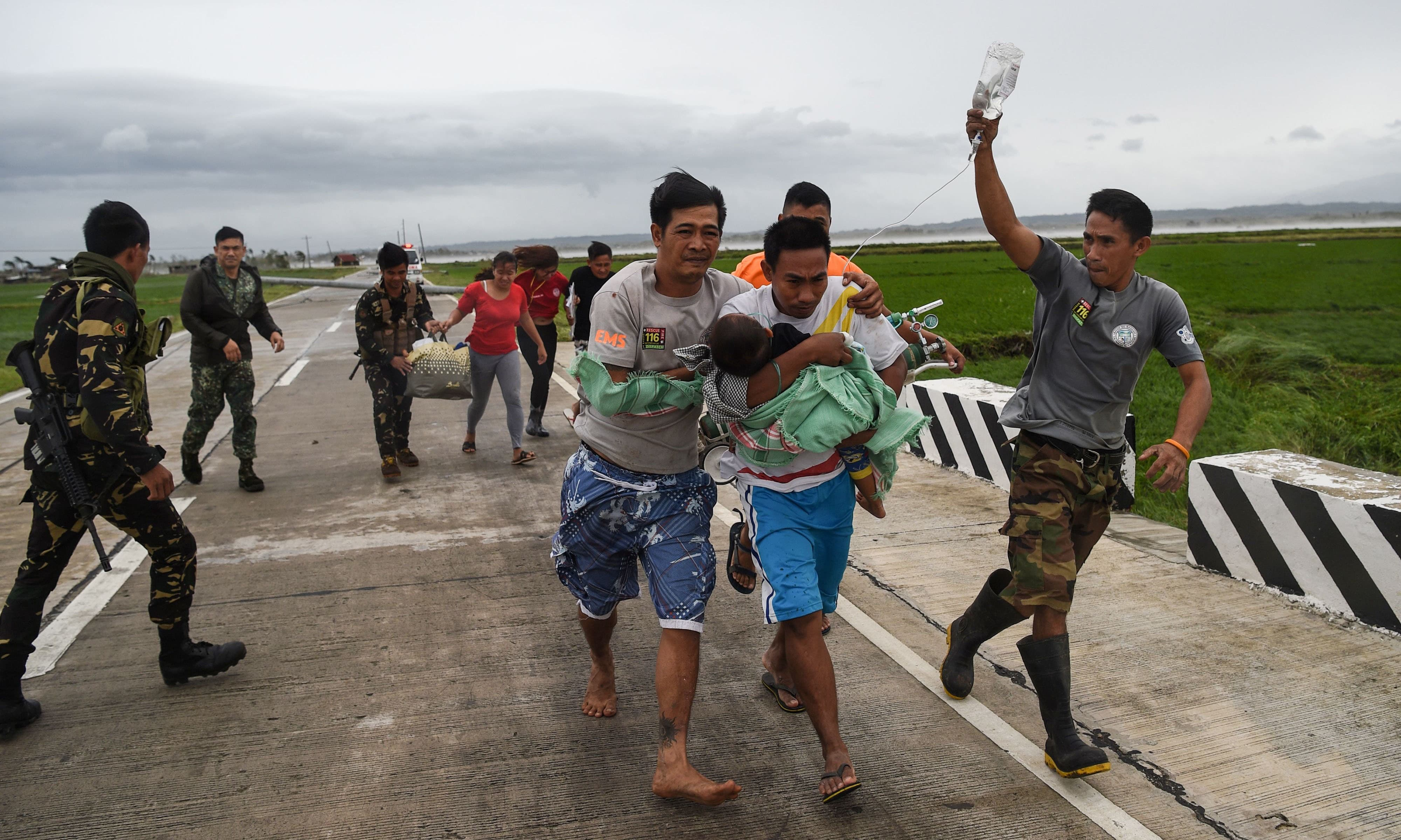 Philippine soldiers assist a family carrying their sick child to a waiting government vehicle after their ambulance failed to make it through a road blocked with fallen tree debris and electric posts toppled by strong winds from Super Typhoon Mangkhut in Baggao town, Cagayan province. — AFP