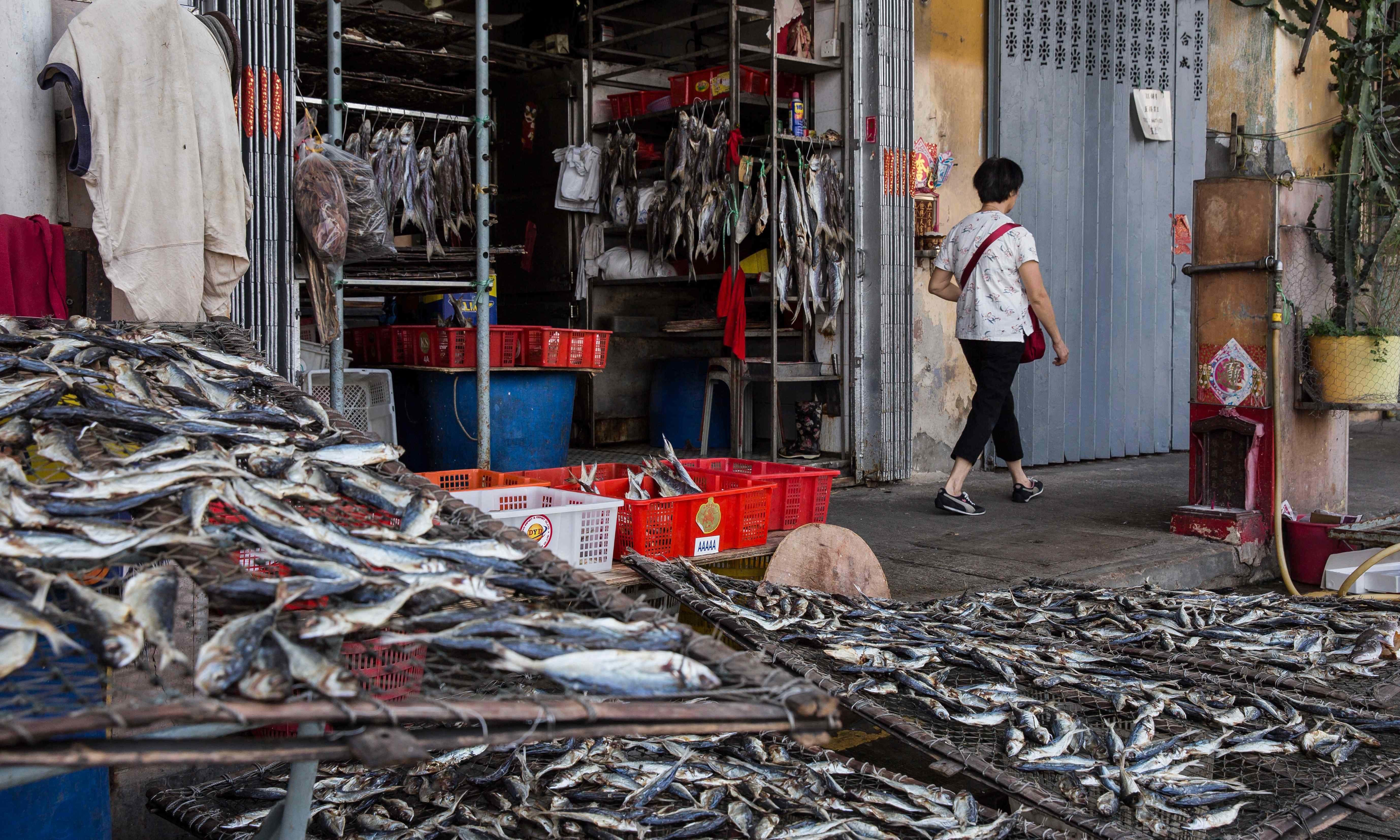 A pedestrian (R) walks past a shop selling dried fish before the expected arrival of Super Typhoon Mangkhut in Macau — AFP
