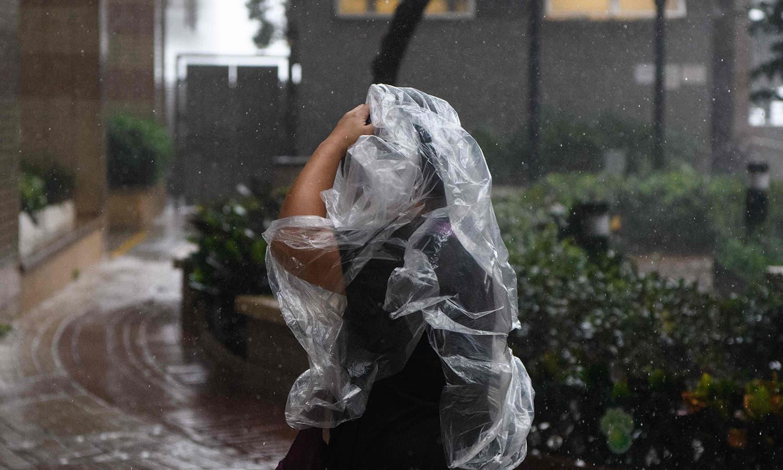 تیز  بارش سے بچنے کے لیے ایک  راہگیر نے خود کو پلاسٹک سے ڈھانپا رکھا ہے — فوٹو : اے ایف پی