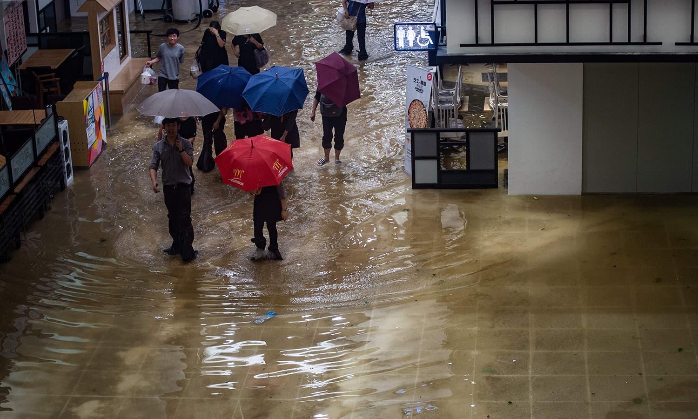 ہانگ کانگ اور چین میں طوفان اور بارش سے آنے والے سیلاب کے باعث کئی علاقے زیر آب آگئے— فوٹو : اے ایف پی