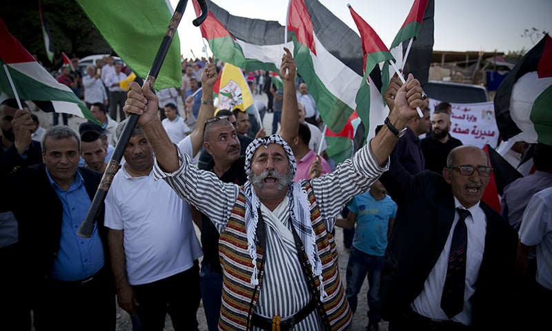 Palestinians protesters fly national flags and chant anti Israel slogans in the West Bank hamlet of Khan al-Ahmar , Sunday, Sept. 16, 2018. —AP