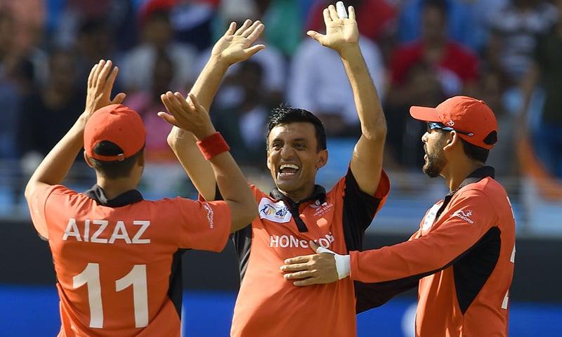 Hong Kong cricketer Ehsan Khan (C) celebrates with teammates after dismissing Indian cricket team captain Rohit Sharma. —AFP