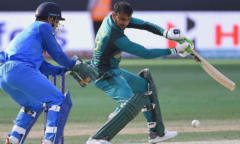 Malik plays a shot as as Indian wicketkeeper Mahendra Singh Dhoni (L) looks on — AFP