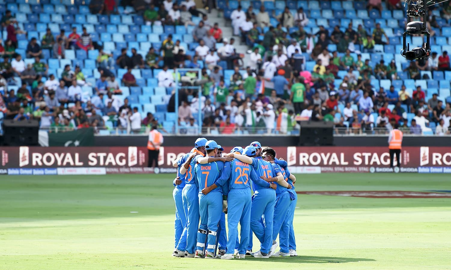 Indian team stand in a huddle before the start of the match between Pakistan and India at the Dubai International Cricket Stadium. — AFP