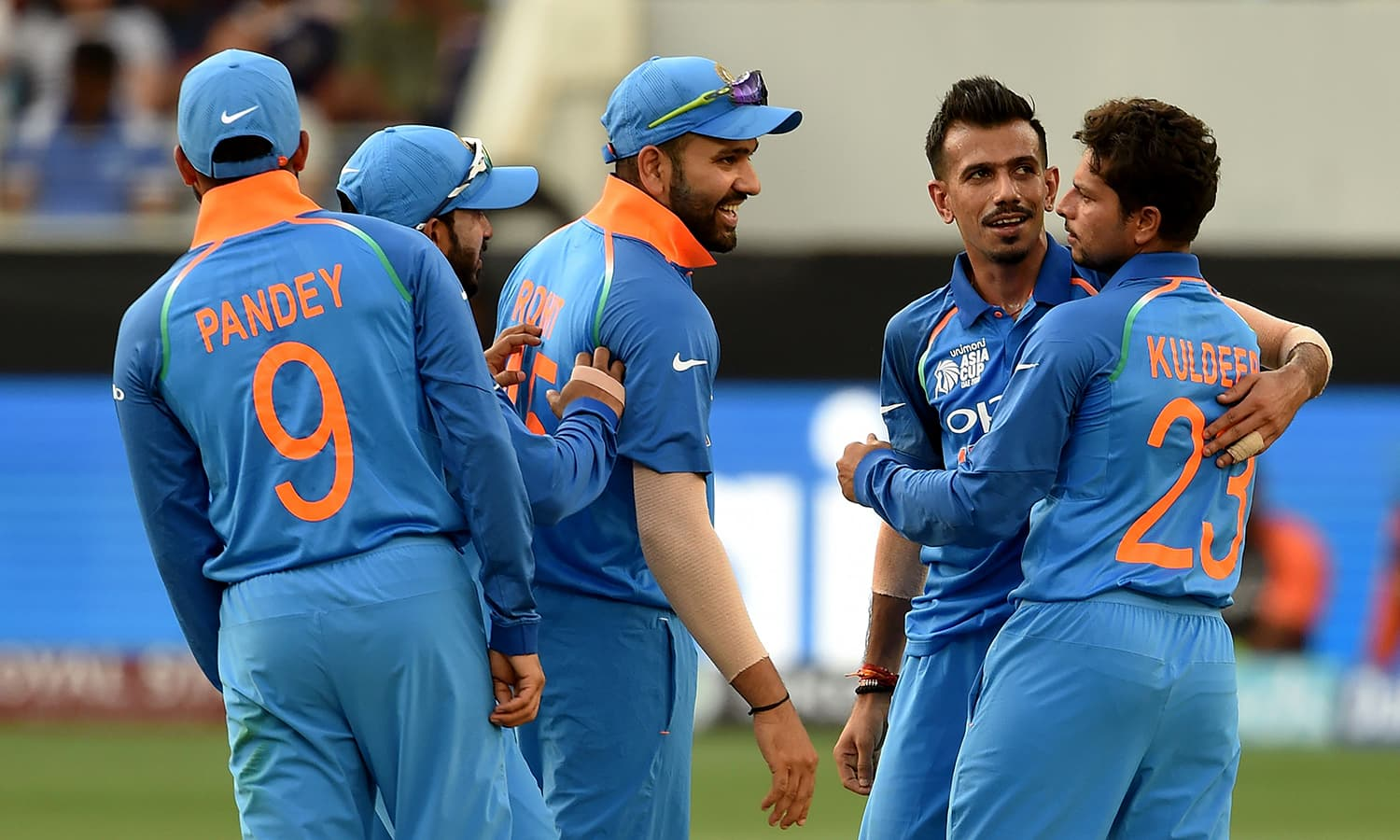 Indian cricketer Kuldeep Yadav (R) celebrates with teammates after dismissing Pakistan batsman Babar Azam. — AFP