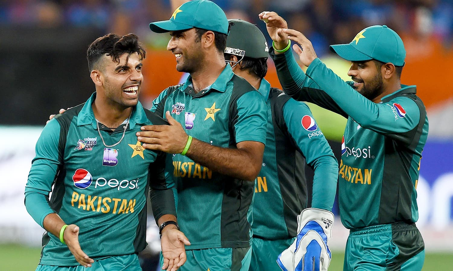 Pakistan cricketer Shadab Khan (L) celebrates with teammates after he dismissed Indian cricket team captain Rohit Sharma. —AFP