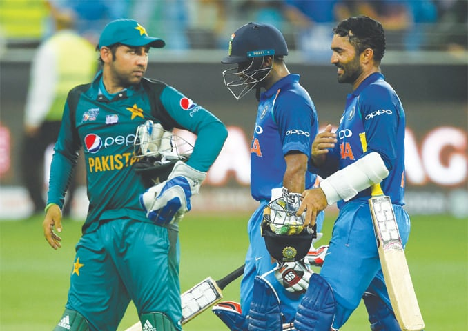 PAKISTAN's captain Sarfraz Ahmed leaves the field followed by India's Dinesh Karthik (right) and Ambati Rayudu at the end of the one-day international Asia Cup match at the Dubai International Cricket Stadium on Wednesday.—AFP