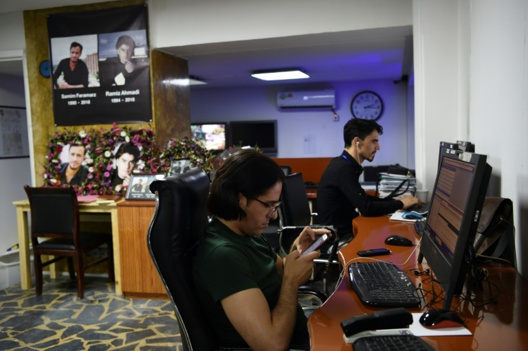 In the Tolo News office in Kabul, reporters work beside photo tributes to two colleagues killed in a suicide attack in September. ─ AFP