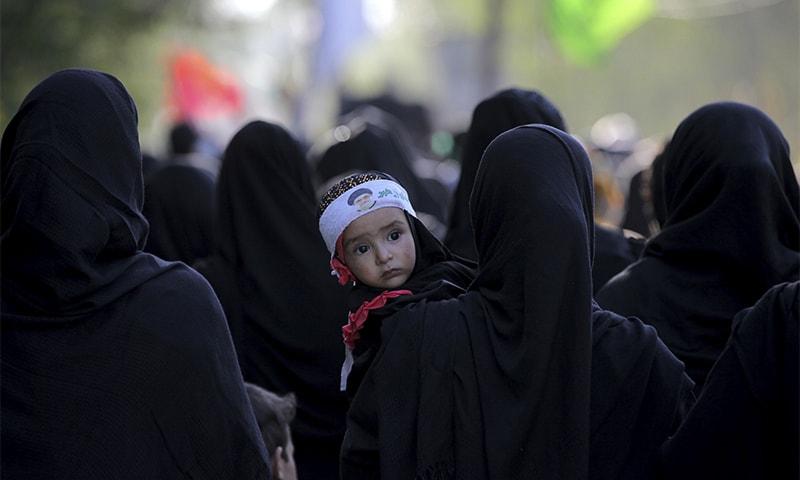 A Kashmiri Shia woman holds a child as she participates in a Muharram procession in Srinagar. ? AP