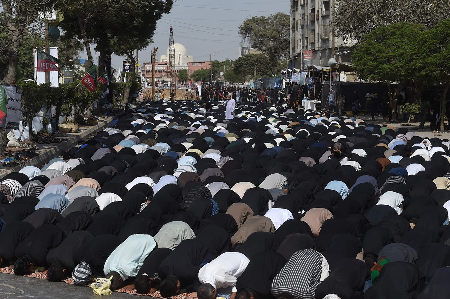 Mourners offer noon prayers during a religious procession in Karachi.— AFP