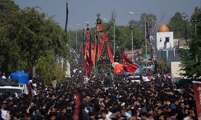 Mourners parade during a procession on the ninth of Muharram in Islamabad. — AFP