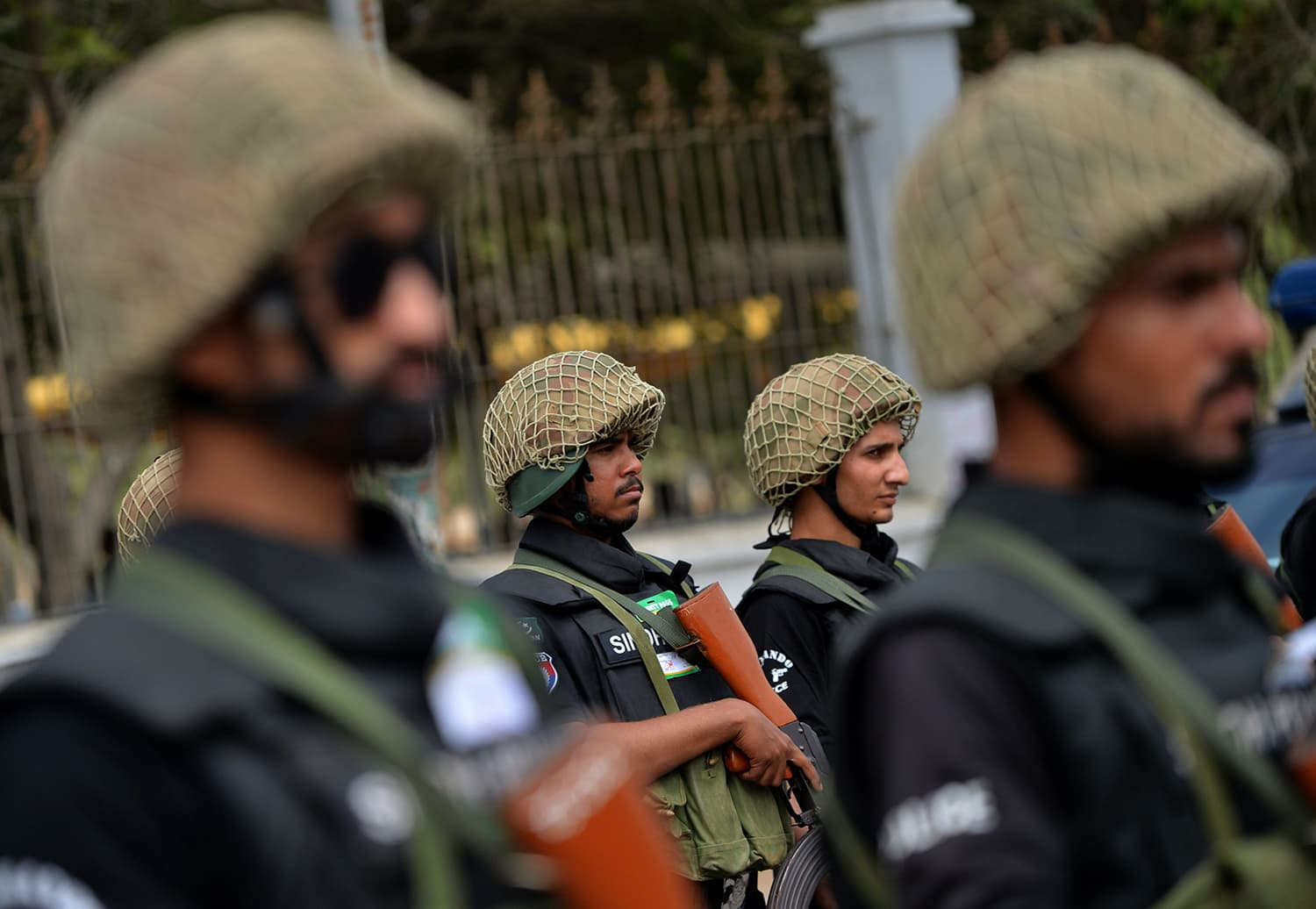 Security personnel stand guard along the side of a road during a procession in Karachi. — AFP
