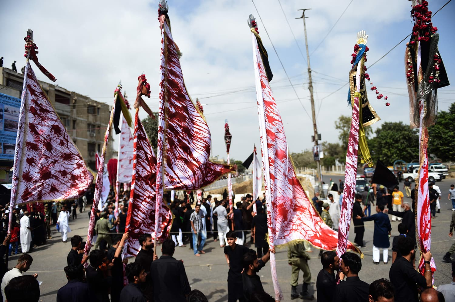 Mourners carry religious flags during a procession in Karachi. — AFP