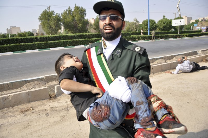A Revolutionary Guard member carries a wounded boy after a shooting during a military parade marking the 38th anniversary of Iraq's 1980 invasion of Iran on Saturday. — AP