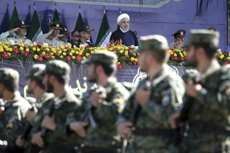 Iran's President Hassan Rouhani, top center, reviews army troops marching during the 38th anniversary of Iraq's 1980 invasion of Iran on Saturday. ─ AP