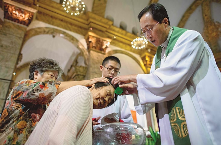 BEIJING: A priest baptises a woman after a mass at the  the state-run South Cathedral on Saturday.—AFP