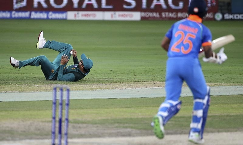 Imamul Haq, left, falls on the ground to stop the ball after a shot played by India's Shikhar Dhawan, right — AP