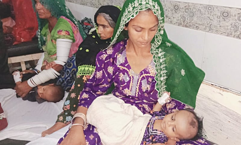 A THARI woman takes care of her ailing child at the Mithi Civil Hospital on Sunday.—Dawn
