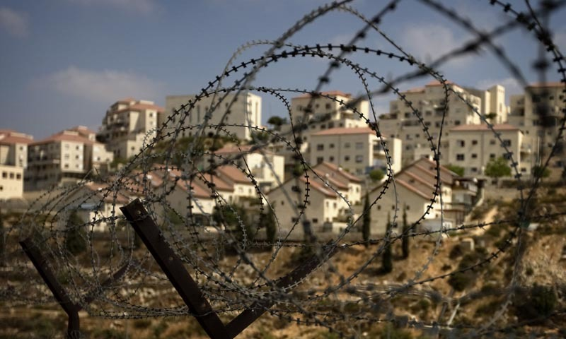 The West Bank Jewish settlement of Beitar Ilit is seen through a barbed wire fence.— AP/File