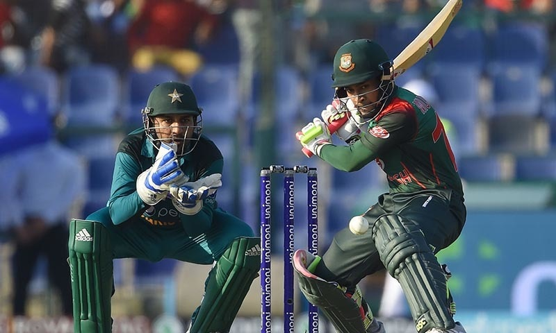 Bangladesh batsman Mushfiqur Rahim plays a shot as Pakistan captain and wicketkeeper Sarfraz Ahmed (L) looks on. — AFP
