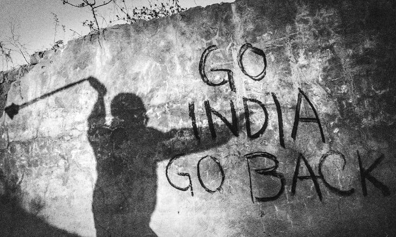 The shadow of a Kashmiri protestor throwing stones at Indian soldiers on a wall marked with an anti-India graffiti. — Photo by Showkat Nanda