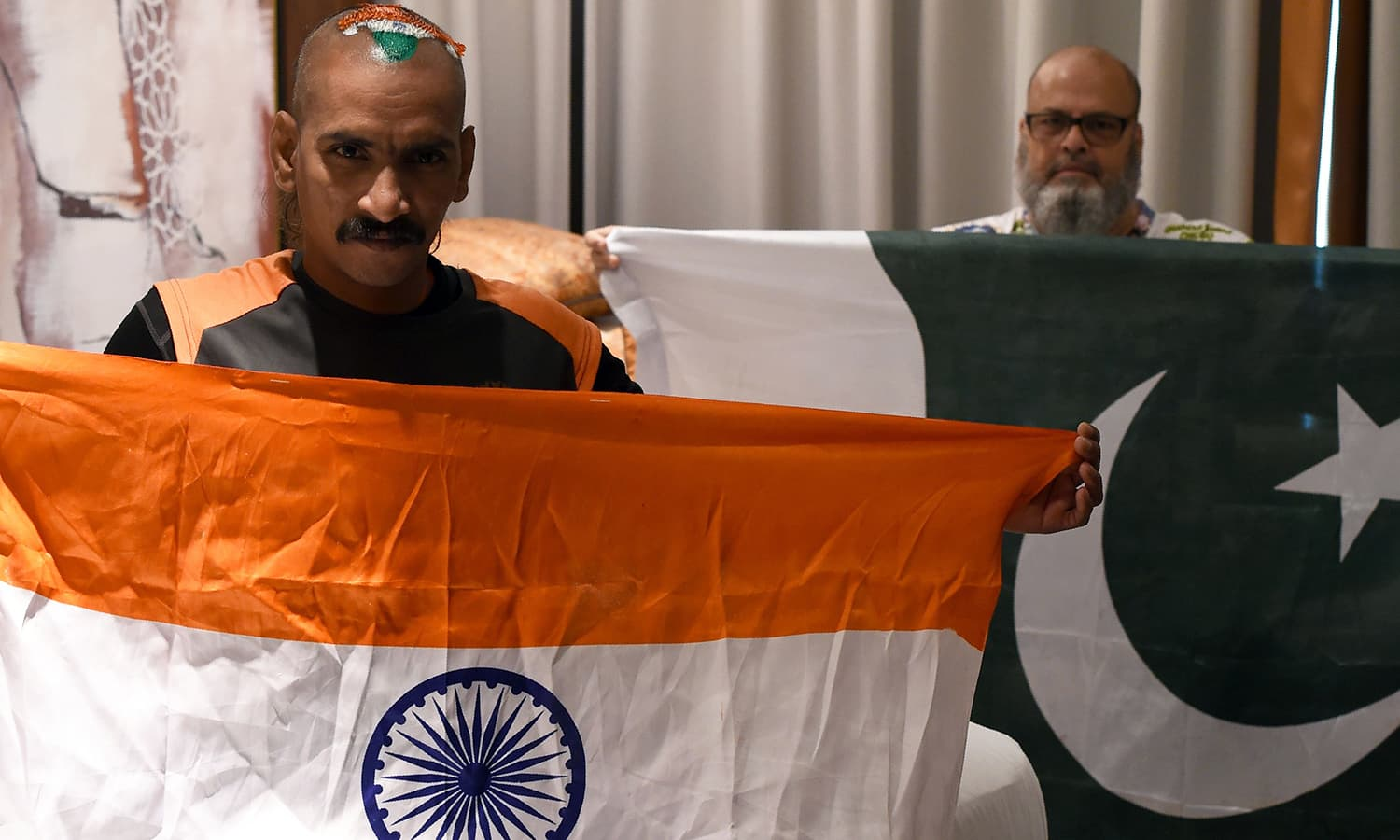 Indian cricket fan Sudhir Kumar (L) and Pakistan cricket fan Mohammad Basheer hold their respective national flags as they pose for a picture at a hotel in Dubai in this photo taken on Sept 19, 2018. — AFP