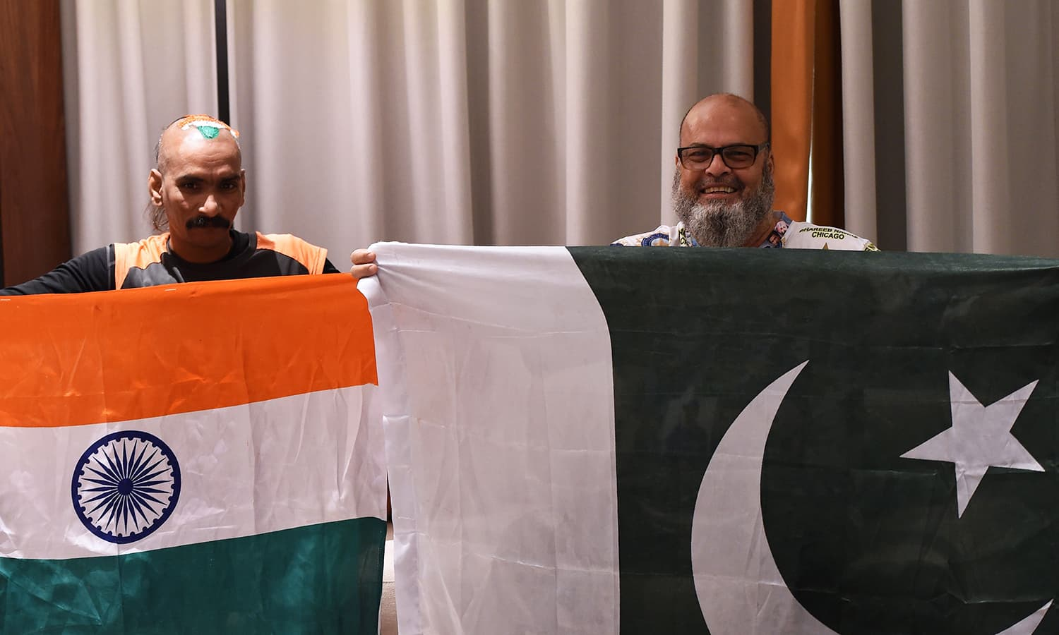 Sudhir Kumar (L) and Pakistan cricket fan Mohammad Basheer hold their respective national flags as they pose for a picture at a hotel in Dubai. — AFP