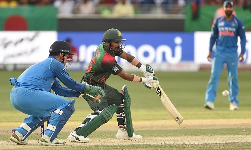Bangladesh batsman Liton Das plays a shot as Indian wicketkeeper Mahendra Singh Dhoni (L) looks on. — AFP