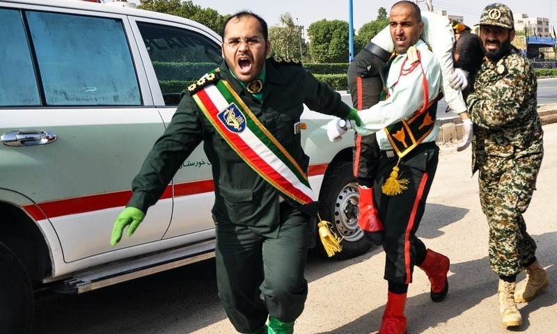 A Iranian soldier carrying an injured comrade at the scene of an attack on a military parade on September 22. — AFP/File