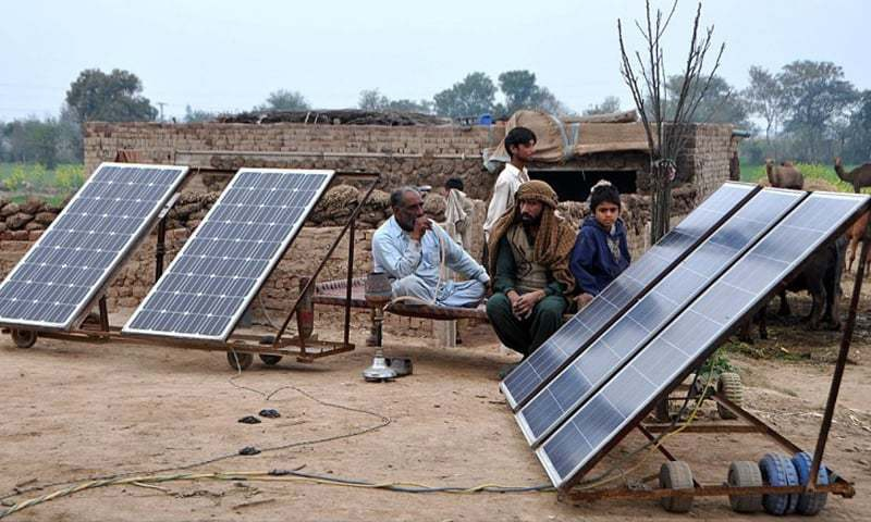 Villagers relax on a farm outside Sheikhupura next to their panels. Official estimate based on household surveys suggests that about 5 million people remained off-grid in 2016.—file photo