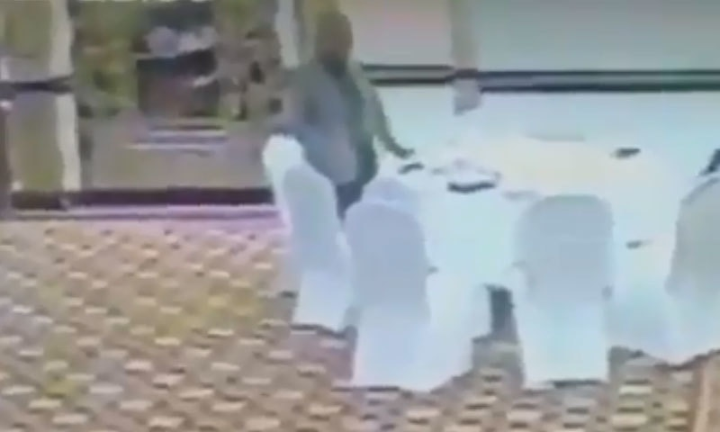 The officer, seen in this still from a CCTV camera picking up a Kuwaiti official's wallet, has been suspended. Photo: Dawn.com