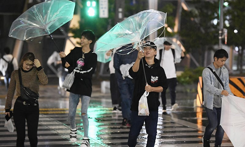 People walk against strong wind as a typhoon approaches in Nagoya, central Japan, Sunday, September 30, 2018. —AP