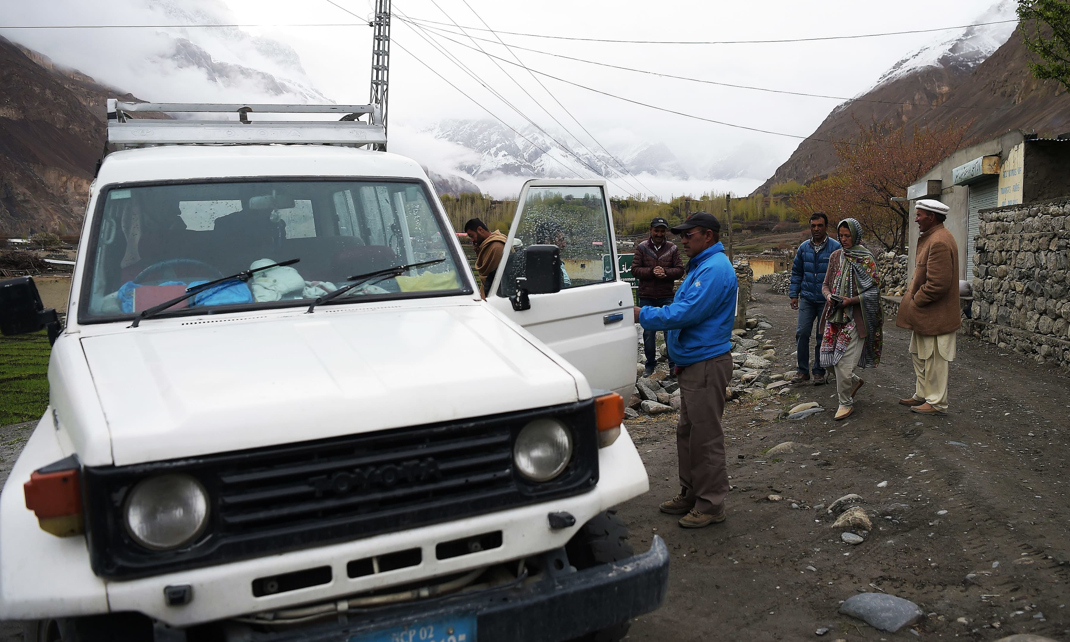 Driver Mirza Aman assists local passengers to board his vehicle in Shimshal valley of Hunza district. —AFP