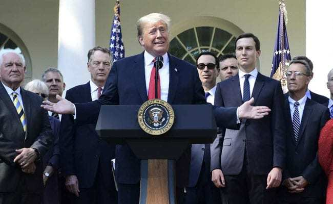 Donald Trump surrounded by staff holds a press conference on the United States-Mexico-Canada Agreement at the White House Rose Garden on Monday. — AFP