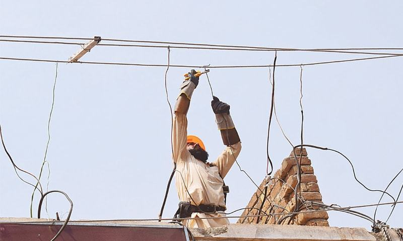 In this file photo a Pesco worker removes illegal connections during a drive in Peshawar. Receivables from 5.3m defaulters currently stand at Rs404.8bn or 49pc of the total outstanding balance.