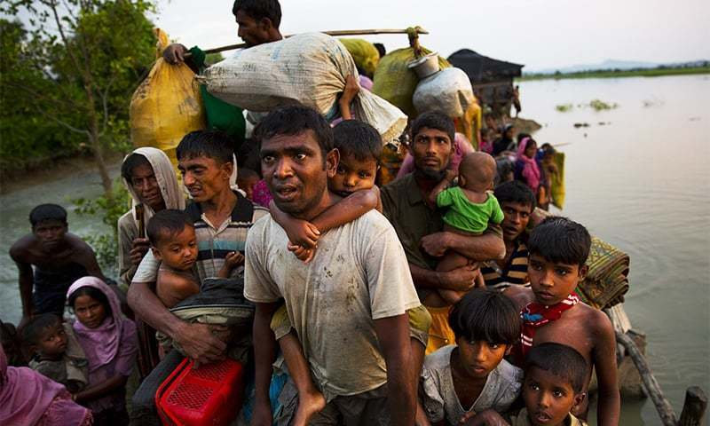 In this Nov 1, 2017, file photo, Rohingya Muslims carry their young children and belongings after crossing the border from Myanmar into Bangladesh, near Palong Khali, Bangladesh.