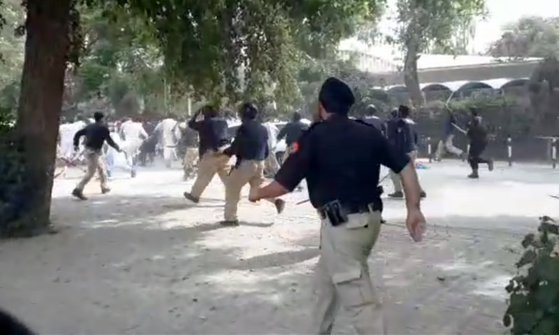Police officers rush towards protesting students to disperse them. —DawnNewsTV