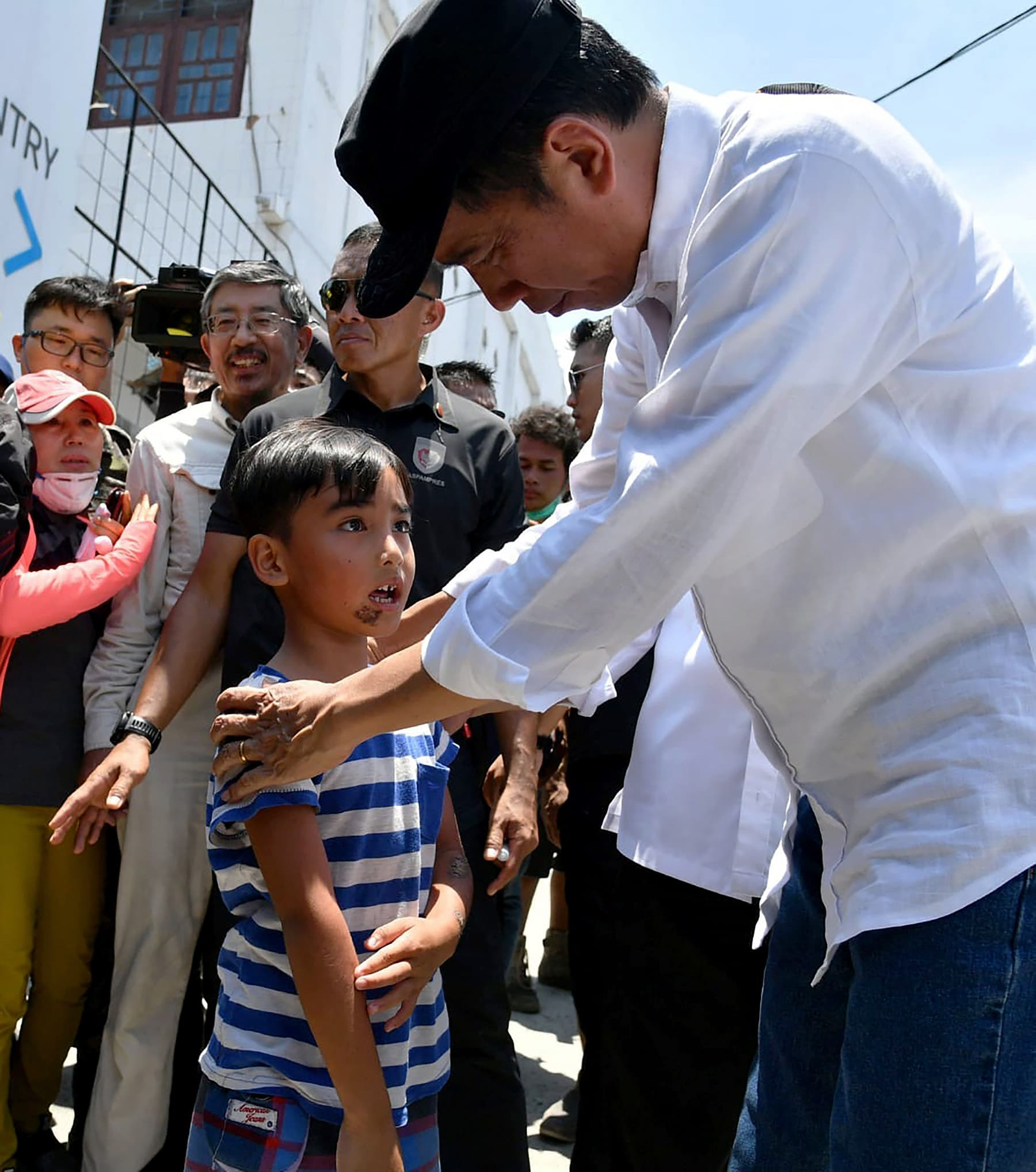 Indonesia's President Joko Widodo meeting a boy who survived the September 28 earthquake and tsunami in Palu in Central Sulawesi. — AFP