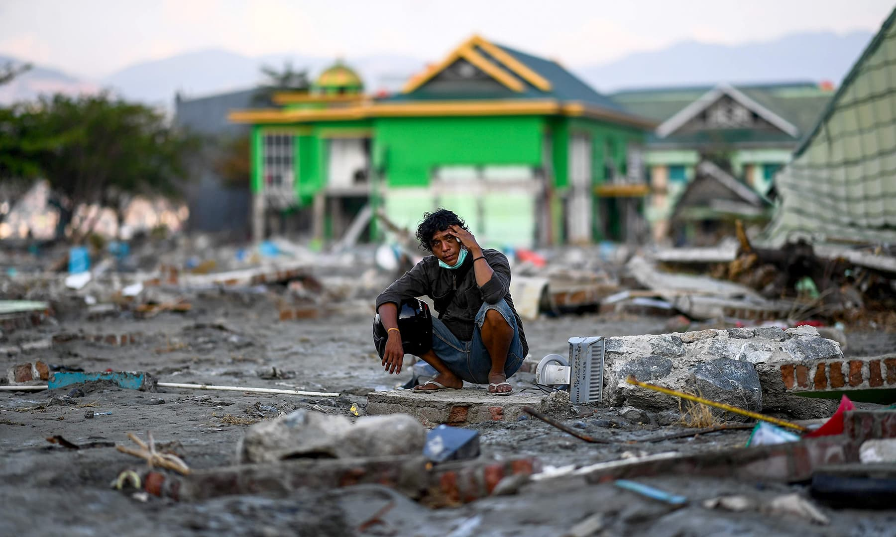An earthquake-affected man sits on the rubble of a house in Palu in Indonesia's Central Sulawesi. — AFP