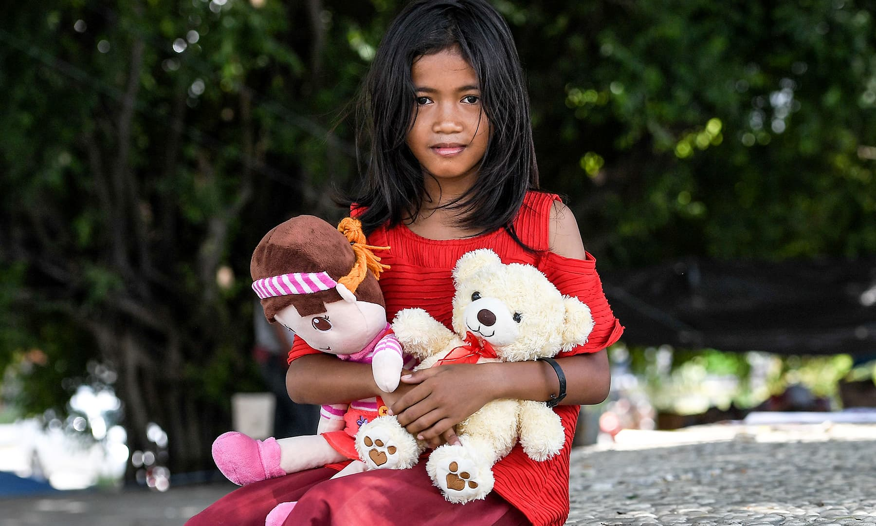A girl poses with her dolls at an evacuation centre in Palu in Indonesia's Central Sulawesi. — AFP