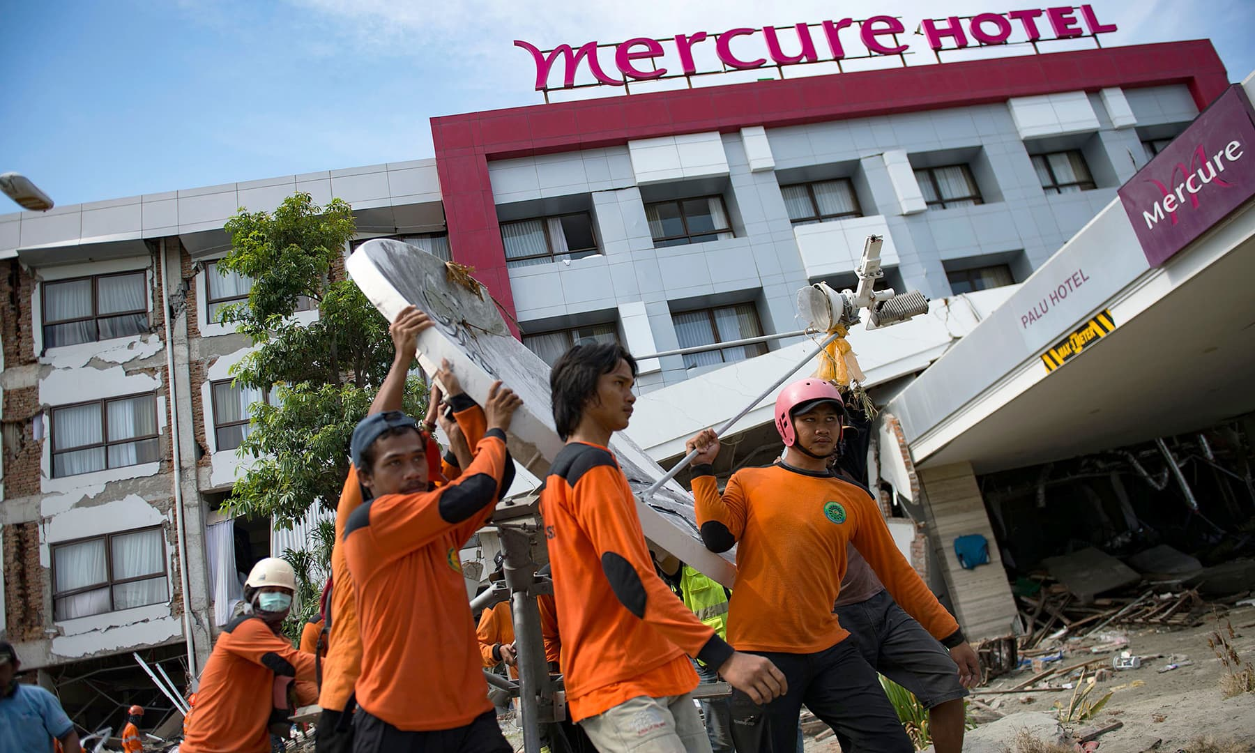 Members of a search and rescue team clear a way to remove victims from the badly damaged Mercure hotel in Palu in Central Sulawesi. — AFP