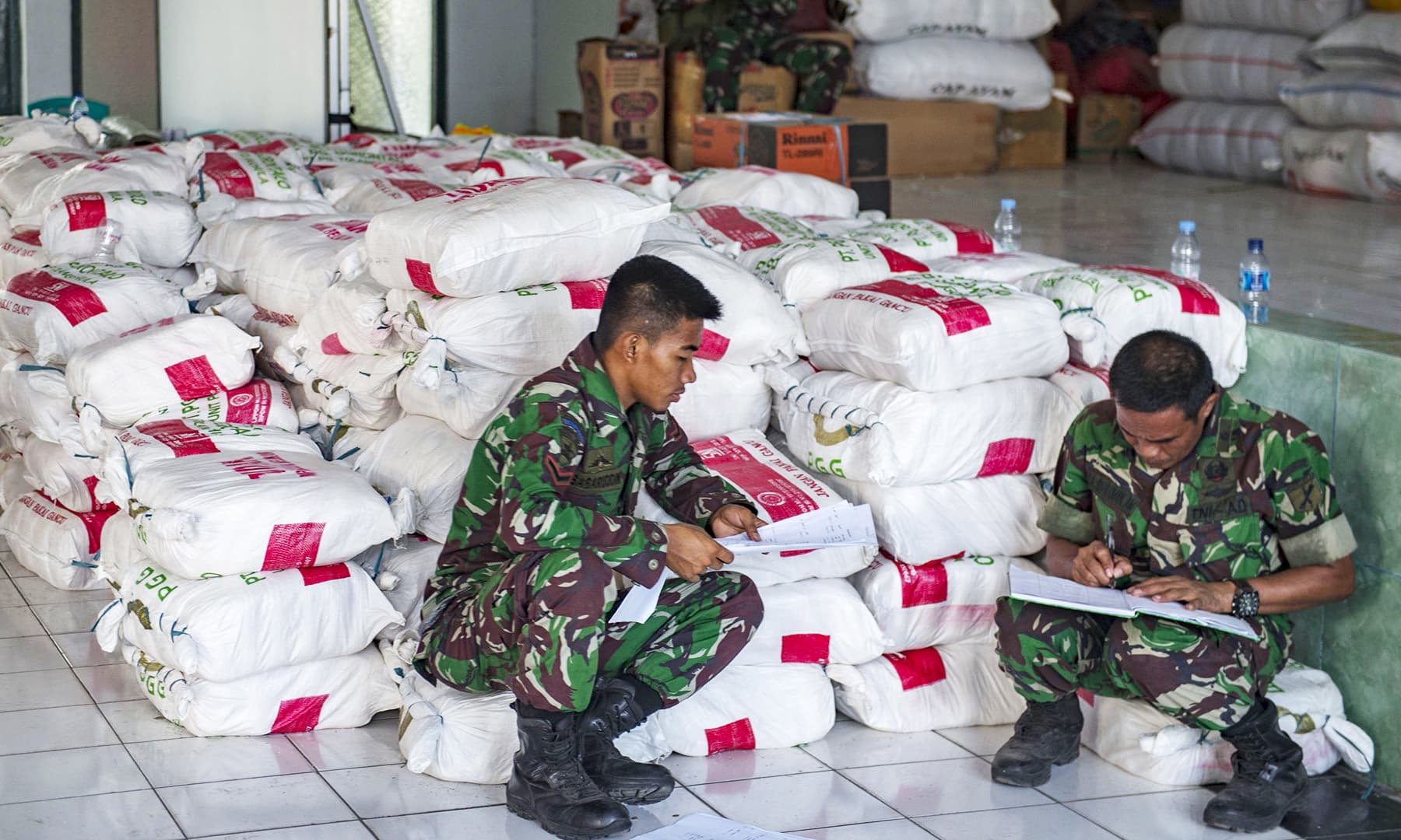 Military officers make a record on relief aim that arrived at the Palu military command before being distributed to earthquake and tsunami victims. — AFP