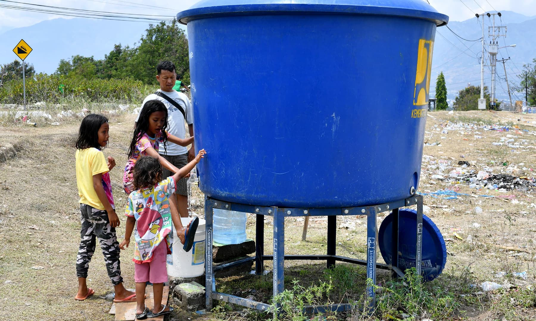 Children access usable water at a temporary camp in Palu in Central Sulawesi. — AFP