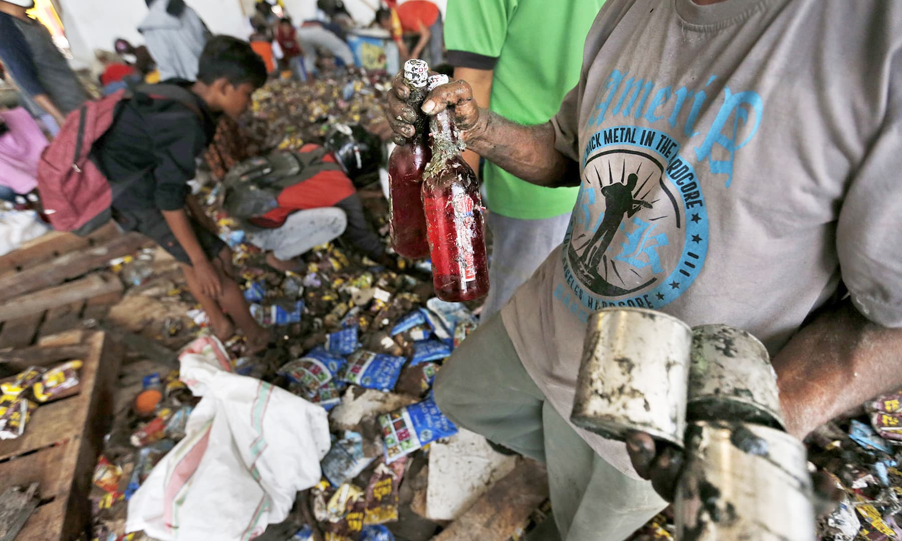 A man holds bottles of syrup and cans of condensed milk scavenged from an abandoned warehouse. — AP