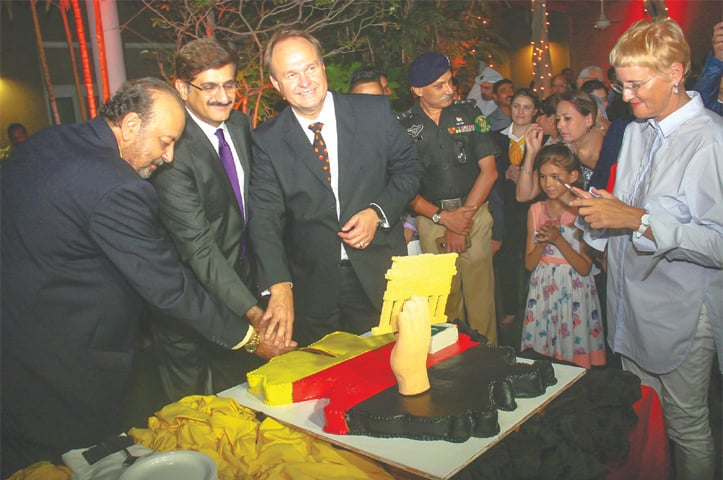 THE chief minister, accompanied by the German CG and speaker of the Sindh Assembly, cuts a cake to mark Unity Day on Wednesday.—White Star