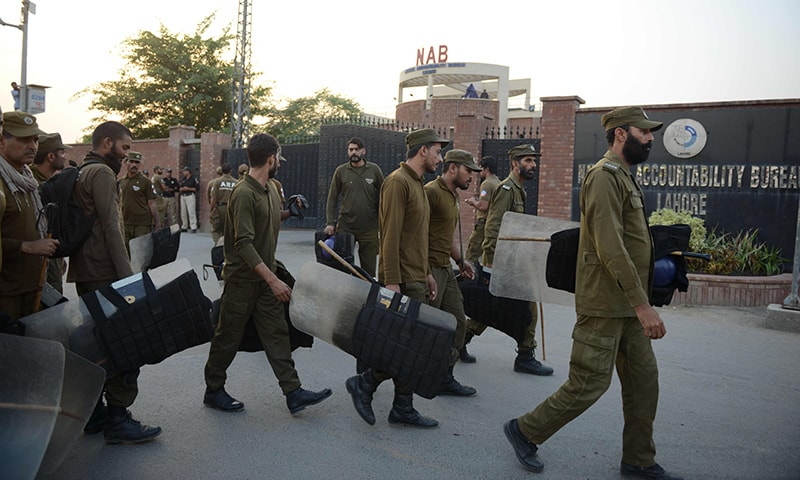 Policemen patrol outside the NAB office following Shahbaz's arrest. — AFP