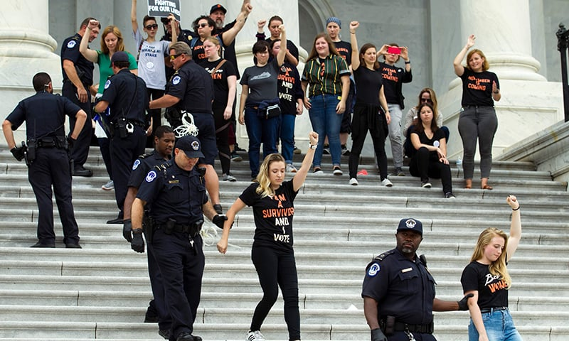 Demonstrators are arrested on the steps of the US Capitol as they protest against Kavanaugh's appointment in Washington DC. — AFP